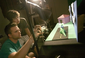 by: JAIME VALDEZ, Adam Thomas (left) gets some pointers from Greg Winterrowd on how to take still shots that will later be used to create a claymation flick.