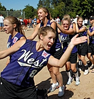 by: JIM KENCK, EVERYBODY CONGA — Murrayhill's Kirsten Fahlbusch (left) hams it up during a post-tournament conga line at the Little League Juniors Softball World Series in Kirkland, Wash.