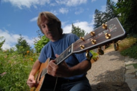"by: Vern Uyetake, John Nilsen, an internationally famous musician, plays ""Silvertime"" on his guitar at his home in West Linn. Nilsen will release his latest CD, shown below, on September 12."