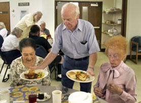 by: Jaime Valdez, FOOD SERVICE – Tom Breen, who volunteers at the Sherwood Senior Center, serves lunch to Sung Lee (left) and Marguerite Poleo on Wednesday.