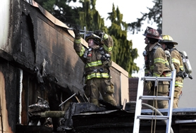 by: Jaime Valdez, Tualatin Valley Fire & Rescue firefighters look for hotspots on the roof of one of the buildings which served as a classroom at the old Tualatin Elementary School on Southwest Boones Ferry Road. The fire started around 2:15 p.m. Thursday.