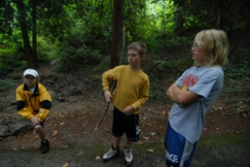 by: Vern Uyetake, Hallinan Elementary School students, from left, Jake McKee, Marcus Wheeler and Jack Schwarz stand in a wooded area outside of the school near the spot where they found three guns on Monday.