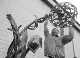 "by: Vern Uyetake, Jerry Knippel, director of special projects for the city of Lake Oswego, demonstrates how a portion of the sculpture ""Connections"" had been broken off the piece last week. A second, similar attachment was also broken and is missing from the piece."