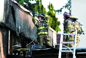by: Jaime Valdez, HOT SPOTS — Firefighters from Tualatin Valley Fire & Rescue look for hotspots on the roof of one of the buildings that served as a classroom at the old Tualatin Elementary school on Southwest Boones Ferry Road. No one was injured in the fire which started around 2 p.m. Aug. 24.