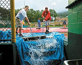 by: JAIME VALDEZ, WET AND WILD — The grounds crew from the Little League International Complex sweeps rainwater from the infield into the first base dugout in Lamade Stadium during Sunday's rain delay.