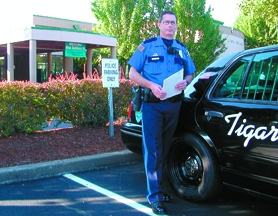 by: Barbara Sherman, THE LAW'S BEHIND HIM — Tigard police officer Dan Gill, who is Tigard High School's school resource officer, holds a copy of a new ordinance that allows police to return truant students to school.