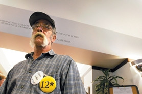 "by: Jaime Valdez, Tom Wallsteed, who used to be homeless, showed his support Tuesday morning in Hillsboro. The button with ""12"" represents the average age of homeless people in the county."