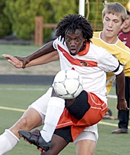 by: MILES VANCE, FOCUSED — Beaverton senior forward Demetri Abraham works to control the ball while pressured by Forest Grove's Erik Laukkanen during the Beavers' 2-1 non-league home win on Monday night.