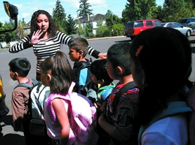 by: Jonathan House, VOLUNTEER — Monica Diaz translates for ESL students at Elmonica Elementary School on bus boarding procedure.