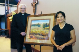 "by: Carole Archer, Father Rick Sirianni of St. Henry Catholic Church and artist Kathy Delumpa Allegri stand next to Allegri's painting ""The Angelus."""