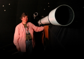 by: patrick sherman, Karen Halliday stands with the observatory's four-inch refractor telescope, ideal for exploring the solar system.