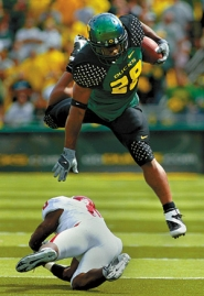 by: L.E. BASKOW, Oregon tailback Jonathan Stewart eludes Oklahoma's Jason Carter in the Ducks' 34-33 win Saturday. Stewart had 144 yards rushing despite playing on a sore right ankle