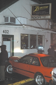 by: Clinton Vining, Passersby look on as police investigate the crash scene at 402 S.E. Main St. Friday night.