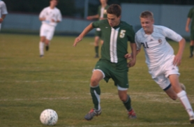 by: Vern Uyetake, West Linn's Drew Tucker attempts to fend off a Clackamas defender in last Tuesday's 4-1 loss to the Cavaliers. Earlier in the week the Lions picked up their first league victory of the season, a 6-0 win over Oregon City.