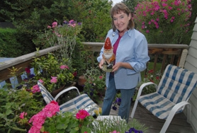 by: Vern Uyetake, Above: Jeannie McGuire's patio is colorful and cozy with plant life. Here she holds Huntly her garden gnome which she carried around in her backpack once she found him on a recent trip to Scotland. The inside of her home is a mini-museum of items from her world travels.