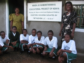 by: Photo contributed by Joyce Maier, A sign hanging in front of Nyakongo Secondary School recognizes those who have given to Wash Jo Humanitarian Outreach