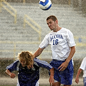 by: MILES VANCE, AHEAD IN THE RAIN — Aloha senior defender Barry Whittlesey heads the ball away from Grants Pass' Dallas Bille during the Warriors' 2-1 home win last Thursday.