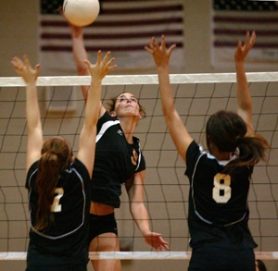 by:  L.E. BASKOW, Central Catholic's Audrey Brockman (middle) spikes a ball over the net between Reynolds' Kelsey Kai (left) and Bonnijien Reams. The Rams won in three games, 25-15, 25-18, 25-16.