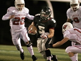 by: jaime Valdez, Tualatin's running back Kyle Johnson drives through a hole in Lincoln's defense in the first half Friday night at Tualatin High School. Lincoln prevailed, 28-7