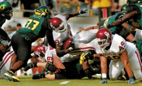 by: L.E. BASKOW, Oklahoma running back Adrian Peterson (with ball) exposed weaknesses in Oregon's defense, running for 211 yards.