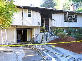 by: Submitted photo, A house on Southwest Nehalem Lane was damaged by fire Tuesday morning. Police are looking for the homeowner, who disappeared after gunshots were reported in the area. A neighbor found bullet holes in his house.