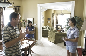by: Chase Allgood of the NewsTimes, Homeowners Scott and Cynthia Kistler, with visitor Kim Morley, show off their home.