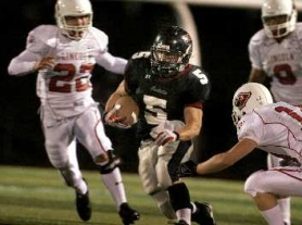 by: Jaime Valdez, LOOKING FOR SPACE — Tualatin senior Kyle Johnson (5) looks for running room in the game with Lincoln.