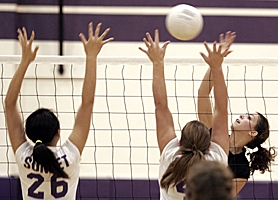 by: JONATHAN HOUSE, WARRIOR ATTACK – Aloha's Niki Naboulsi (right) tries to hit through the Sunset block during her team's Metro loss on Tuesday night.