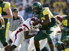 by: JONATHAN FERREY, Running back Chris Vincent, getting stopped by two Washington State defenders in a 2003 game, is back at tailback after two years as a linebacker.