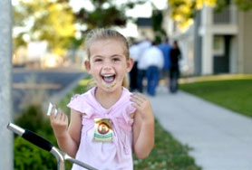 by: L.E. BASKOW, Kylie Cobb, 5, shows off a police-badge sticker given to her Tuesday by North Precinct police Cmdr. Jim Ferraris, who has pledged an additional officer for the city's newest public housing project.