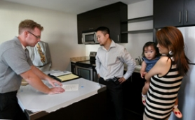 by: L.E. BASKOW, Reed Kirk (left) with Harrison Sales goes over a checklist with Paul, Henna and Jenny Holden for the condo they're buying in the South Auditorium District.