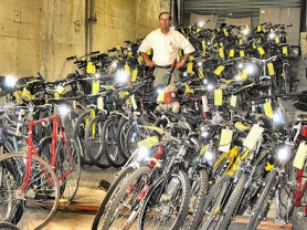 by: Marshall Santos, Bill Swanson, of the Portland Police Bureau's Property and Evidence Division, stands among the dozens of unclaimed bicycles in the division's warehouse. If a bike is unclaimed after 30 days, it will either be sold or thrown away. Recognize one, in this picture?