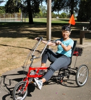 "by: Merry MacKinnon, Reed resident Fran Daggett rode around on a three-wheeled bicycle at Willamette Park last month. As part of a Portland Department of Transportation pilot project called ""the Older Adult Three-Wheeled Bicycle Program"", seven recumbent 21-speed adult tricycles will be at Sellwood Riverfront Park twice a week in October. Seniors are invited to try them out."