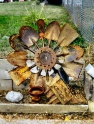 by: Rita A. Leonard, A whimsical sunflower made of car parts and shovels is on display at S.E. 46th and Holgate Boulevard.