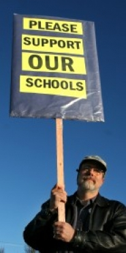 by: JIM CLARK, Rhys Scholes, a parent from Buckman Elementary, drums up support for schools at the intersection of East Burnside Street and Northeast Sandy Boulevard; another grass-roots campaign, Stand for Children, has mobilized in support of the levy on the November ballot.
