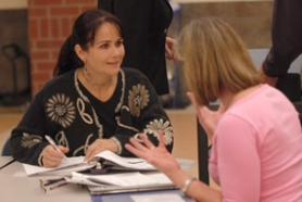 "by: Vern Uyetake, Elementary parents Melanii Lambert and Karen Rathje discuss their handouts during a ""Raising Minds"" session Tuesday at Lake Oswego High School."
