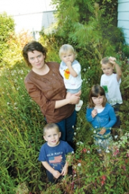 by: Carole Archer, Amy Rose Davis stands with her children in her overgrown front flower bed. She is holding Natalie, 21 months, and her other children are, from left, Sam, 3, Chloe, 5, and Ben, 7.