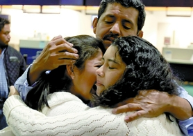 by: Jonathan House, Luis Diaz Sr. and his wife Irma comfort their 11-year-old daughter Jennifer as she prepares to say goodbye. Irma and her two other children, Monica and Luis Jr., boarded a plane late Tuesday night for Guatemala.