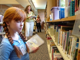 by: Jennifer Clampet, SHELVING FOR THE FUTURE — Emma Patton, 8, and her mother Jennifer shelve books in the children's section of the Tualatin Public Library. The duo began volunteering at the library during the summer.