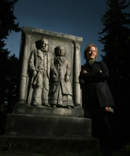 by: JIM CLARK, Mary Miller stands with the headstone of J.B. and Elizabeth Stephens at Lone Fir Cemetery. Miller will lead a cemetery tour on Halloween night.