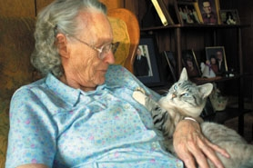 by: Barbara Adams, Estacada-area resident Thelma Ramsey, 89, feeds Kit Kat with pet food delivered by Trudy Hufman, the Estacada Home Delivered Meals Ani-meals driver.