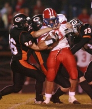 by: CRAIG MITCHELLDYER, Gladstone defenders swarm a La Salle player during Thursday night's game at Gladstone. The Falcons beat the Gladiators 31-21.