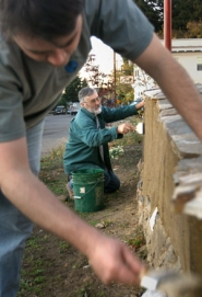 by: JIM CLARK, Volunteers Rick Knight (foreground) and Scott Vala apply linseed oil to a cob wall that's an elemental part of the Arleta Triangle, at Southeast 72nd Avenue and Woodstock Boulevard.