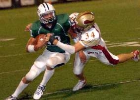 by: DAN BROOD, ON THE MOVE – Tigard quarterback Ryan Gorton (left) looks to escape from Forest Grove's Josh Matiaco.