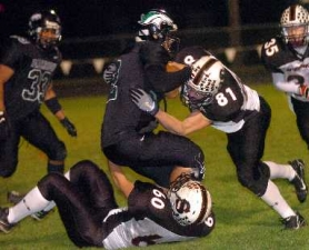 by: DAN BROOD, SACK ATTACK — Sherwood's Spencer Wolfley (81) and Justin Grimes combine to bring down Parkrose quarterback Theron Segar in Friday's contest.