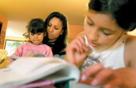 by: Jaime Valdez, KNOWING THE LANGUAGE — Edith Sanchez, of Tigard, watches her youngest daughter Sheyla, 6, read as her oldest daughter Mayte, 12, works on math homework. Sanchez is taking English language classes at the Tualatin Resource Center. She wants to be able to look over her children's schoolwork.