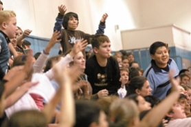 by: Jonathan House, CALLING FOR CANDY — Middle school students attending the Police Activities League kick-off raise their hands and shout out for candy during a presentation Monday. Hundreds of students showed up to learn about the program.