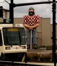 by: L.E. BASKOW, Constructed as a celebration of Oregon's timber industry, Paul Bunyan overlooks a MAX station.
