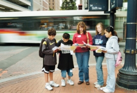 by: Carole Archer, From left, Jon Ronnfeldt,11, Ronald Zialcita, 12, chaperone and parent Angela Ronnfeldt, Merry Bishop, 11, and Marirose Caasi, 11,  regroup at the corner of Southwest Sixth and Salmon to check their street maps and review their 'passports' as a TriMet bus streams by.