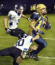 by: Carole Archer, Barlow's Colton Seiler tries to pick up extra yards, while Gresham's Kyle Robinson, 20, tries to pull him to the turf. The Bruins won the game 50-14 on Friday night.
